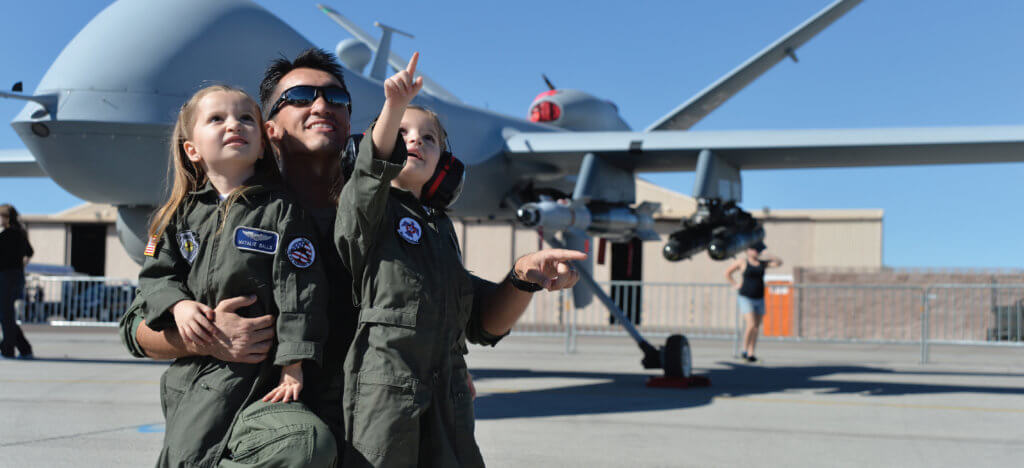 An Air Force pilot and his daughters point to the sky during an activity for Month of the Military Child. Every child in a military family is honored during April.