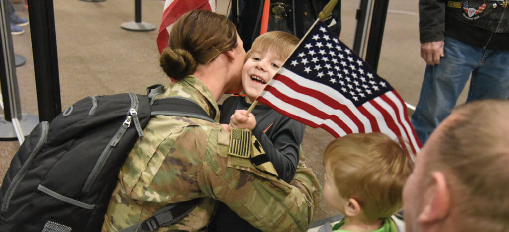 Army National Guard soldier hugs her son upon her return from deployment. MFRI conducts research on military and veteran families to help improve their quality of life.