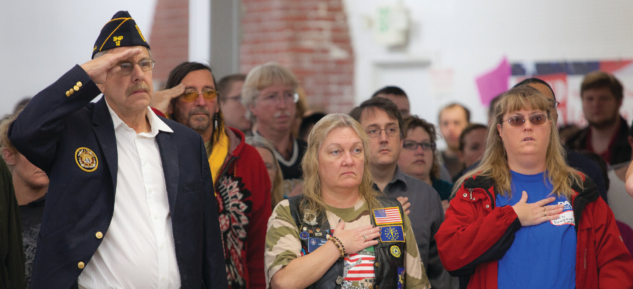 Veterans and volunteers salute the flag at a Stand Down