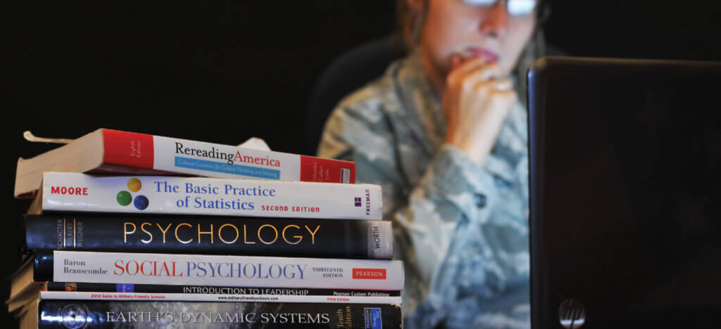Airman works on computer with textbooks nearby