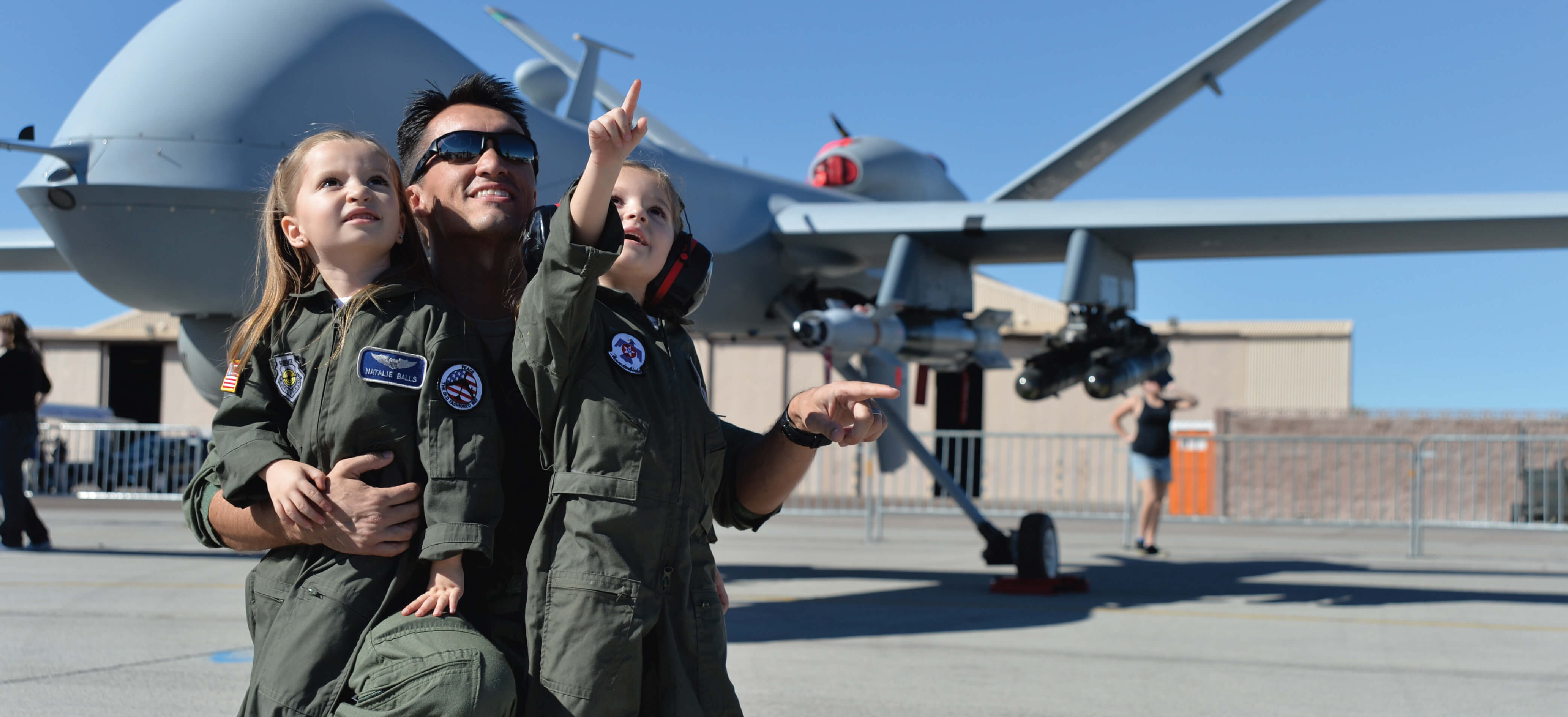 An Air Force pilot points to the sky with his daughters