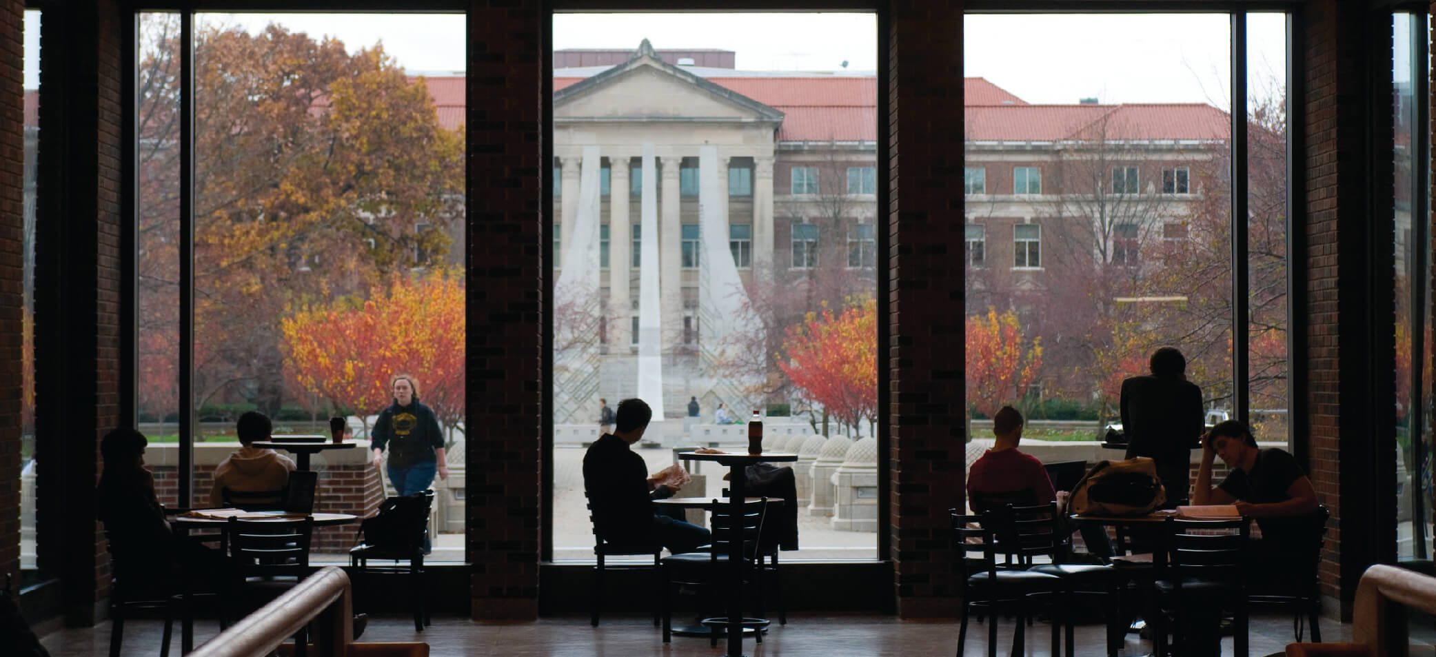 Students study with a window showing Purdue's campus behind them
