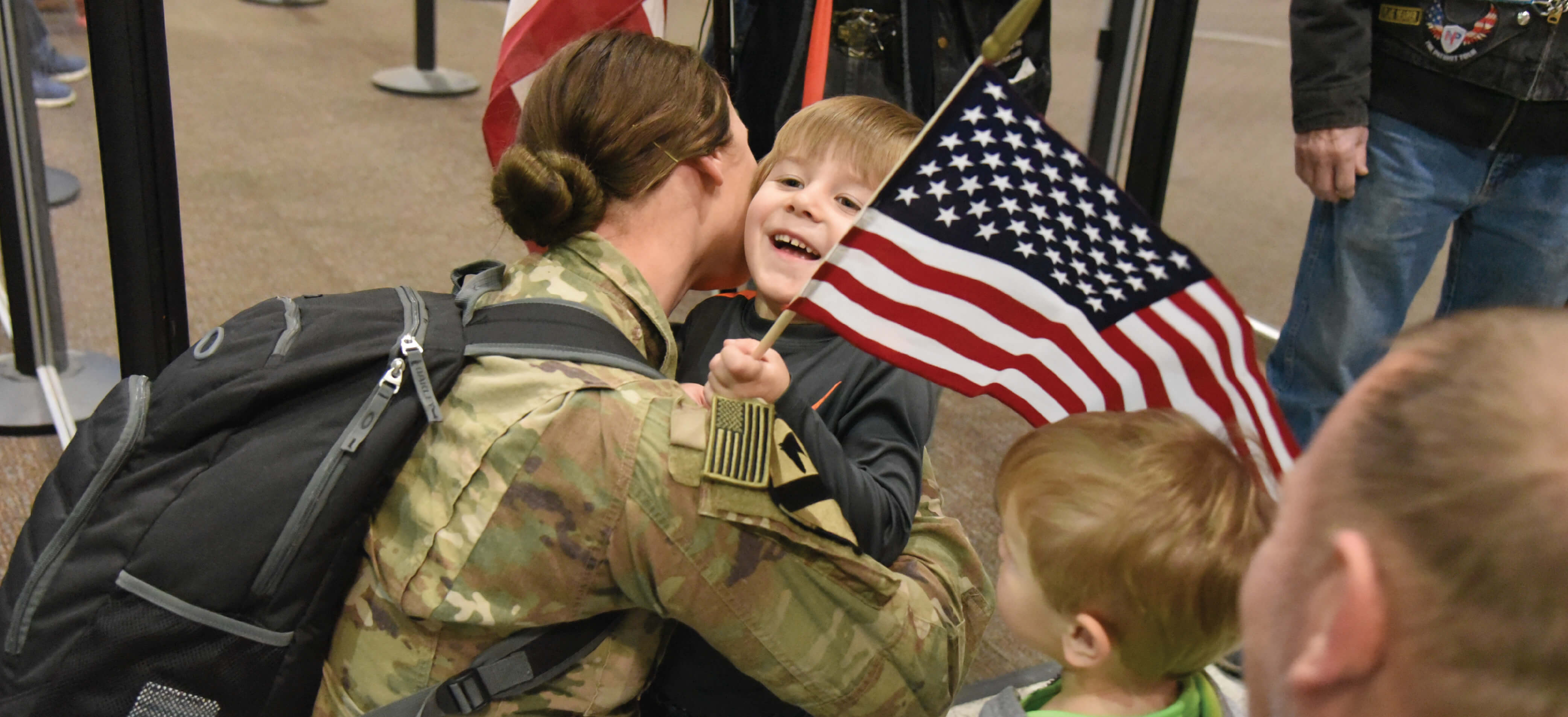 Army National Guard soldier hugs her son upon her return from deployment