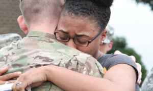 Young woman hugs her Army solider husband