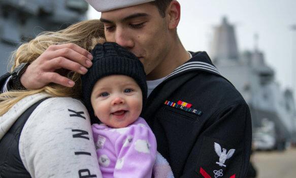 Navy family hugs near the shore