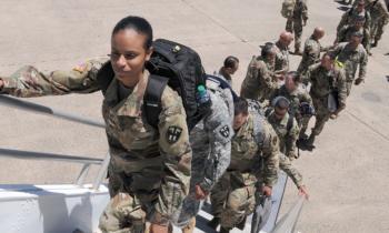 Service members board a plane