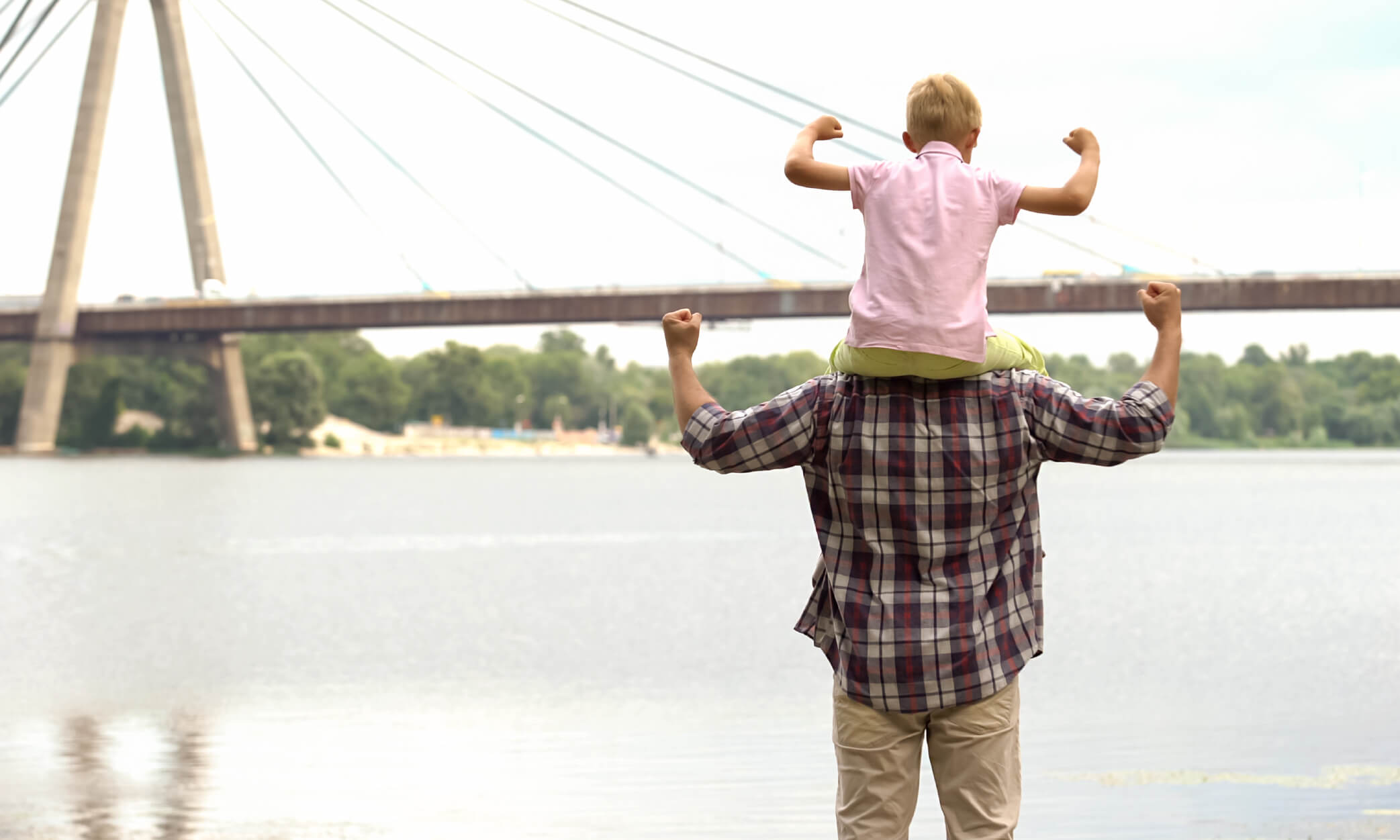 Dad and son in front of bridge showing muscles
