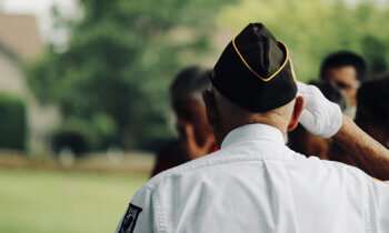 Veteran with POW-MIA patch saluting